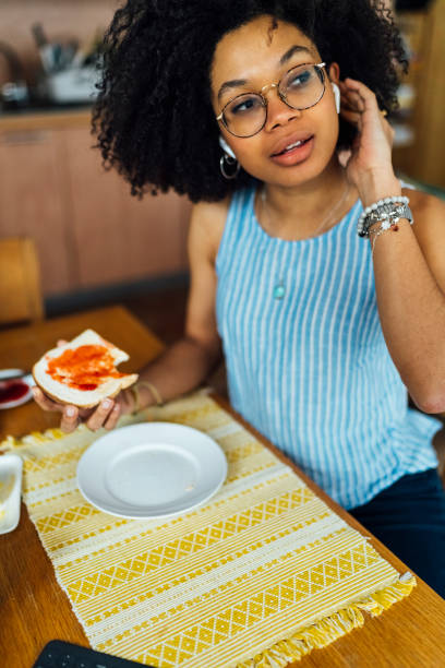 Young woman with curly hair wearing wireless headphones while having breakfast at table