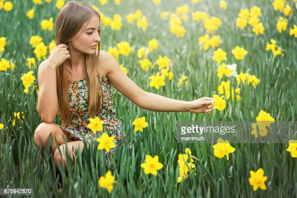 young woman with daffodils - daffodils stock photos and pictures