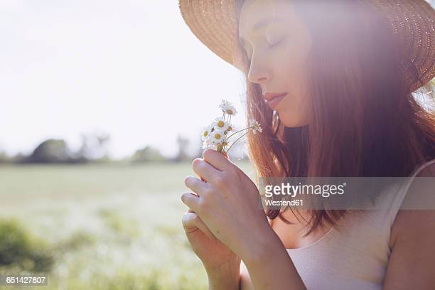Young woman with daisies at backlight