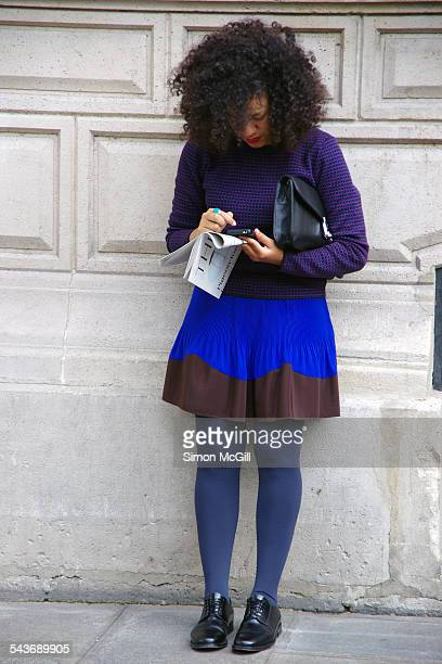 Young woman with dark curly hair hunches over her cellphone texting while leaning against a wall purse under her arm and newspaper in her hand in...