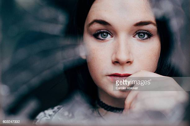 Young woman with dark hair and pale skin looking through broken glass