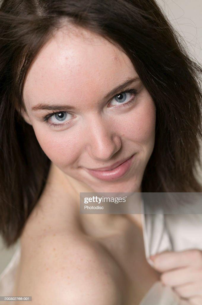 Young woman with dark hair, exposing shoulder, posing in studio, portrait : Stock Photo