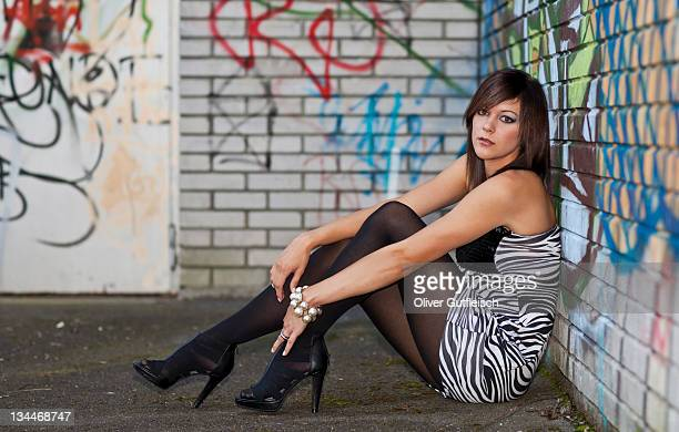 young woman with dark hair wearing a top with a zebra pattern and high heels posing while sitting in front of a wall with graffiti - beautiful women in pantyhose stock photos and pictures