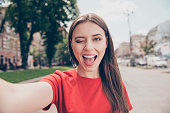Young woman with dark hair winks and wide open her mouth shooting selfie on the front camera of the smartphone