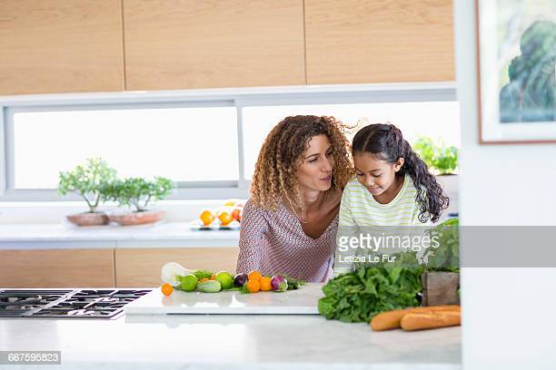 Young woman with daughter in kitchen
