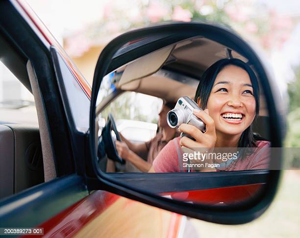 Young woman with digital camera smiling, reflection in car mirror