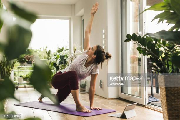 young woman with digital tablet exercising on mat at home - yoga stock-fotos und bilder