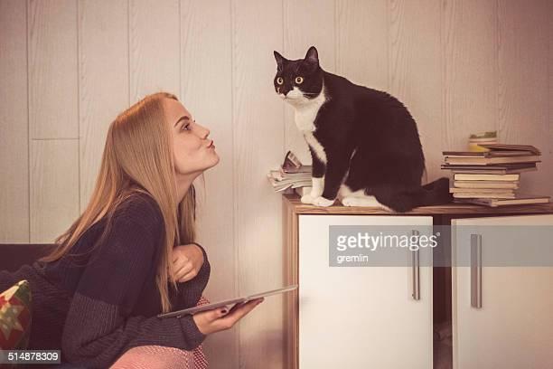 Jeune femme avec tablette numérique de son joli chat animal de compagnie