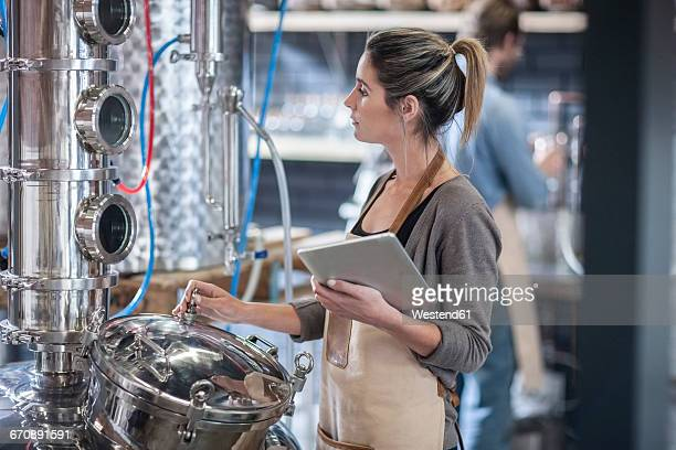 Young woman with digital tablet looking at machine in distillery