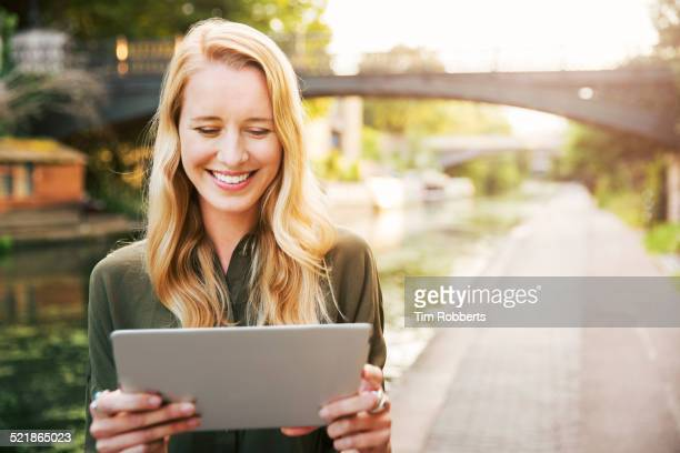 Young woman with digital tablet on canal.