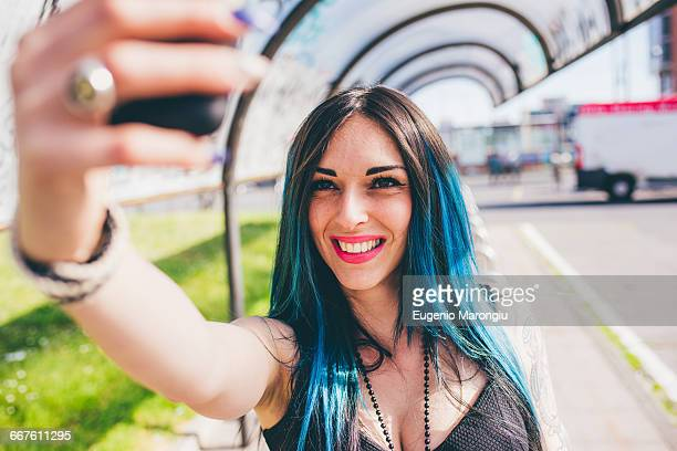 Young woman with dip dyed blue hair taking smartphone in urban bus shelter