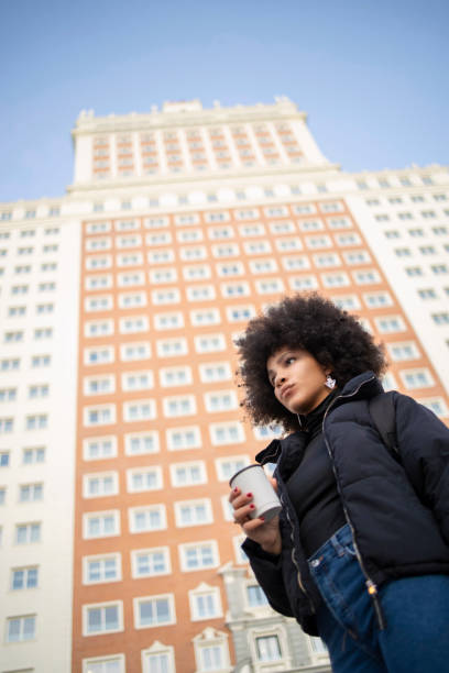 Young woman with disposable coffee cup looking away in city