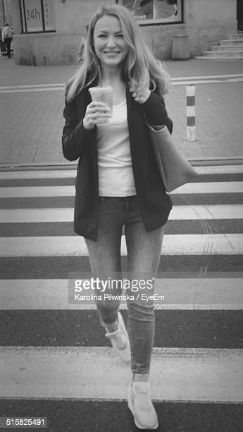 Young Woman With Disposable Coffee Cup Walking On The Street