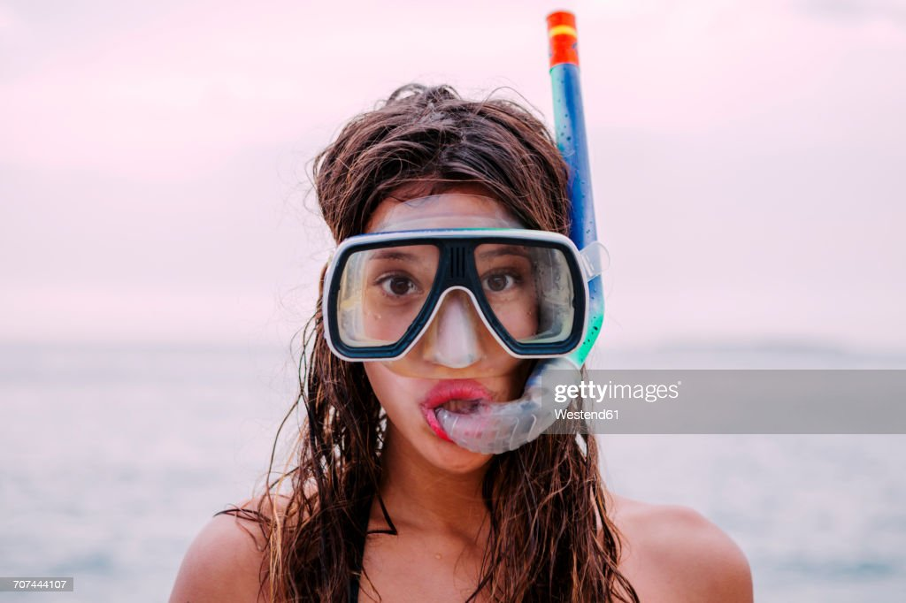 Young woman with diving goggles and snorkel pulling funny faces : Stock Photo