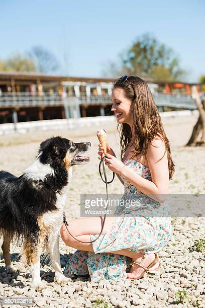 Young woman with dog and ice cream cone outdoors in summer