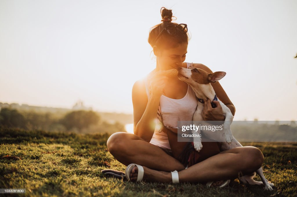 Young woman with dog eating ice cream : Stock Photo