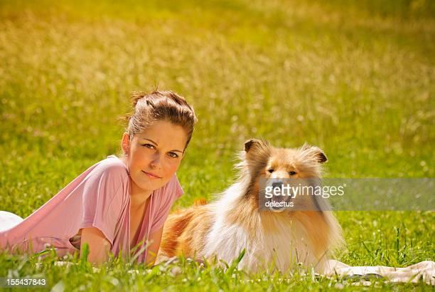 Joven mujer con perro en el sol