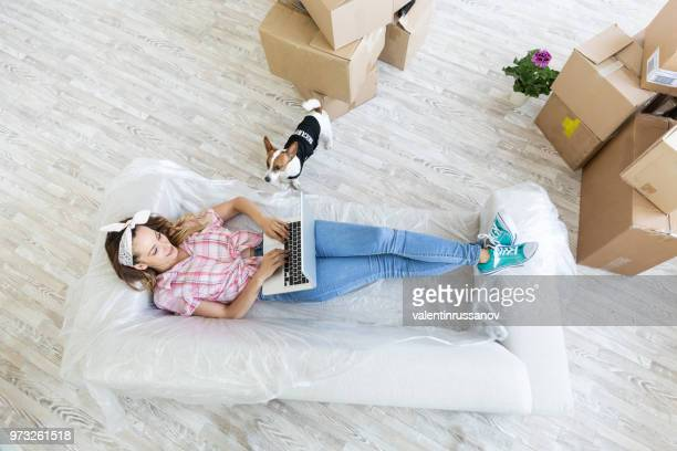 Young woman with dog lying on sofa using laptop