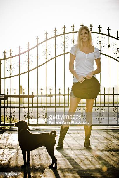 young woman with dog near gate - puggle stock pictures, royalty-free photos & images