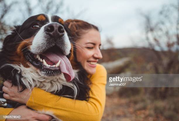 young woman with dog - amor imagens e fotografias de stock