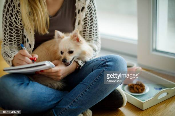 young woman with dog sitting on the floor and writting notes - dog pad foto e immagini stock