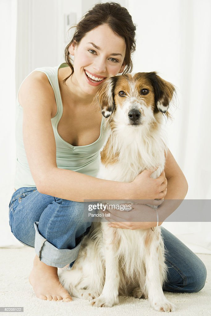 Young woman with dog, smiling : Stock Photo