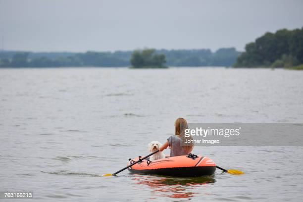 Young woman with dog swimming in inflatable raft