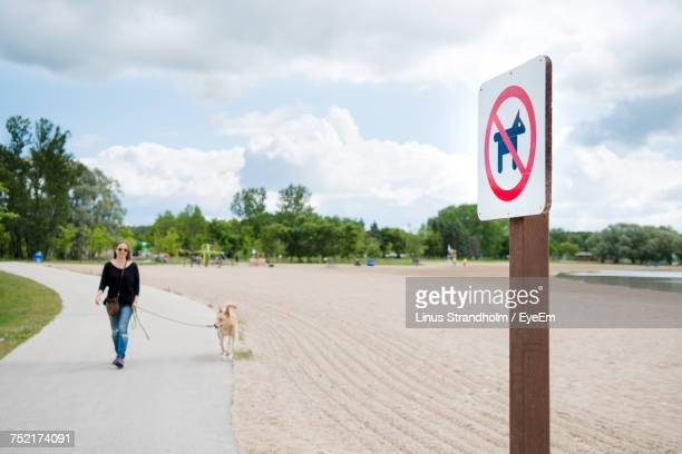 Young Woman With Dog Walking On Road At Park Against Cloudy Sky