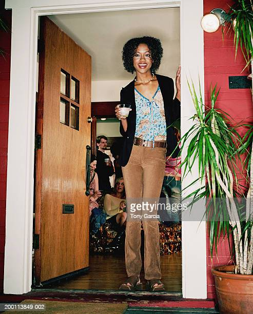 Young woman with drink standing by doorway, friends inside house
