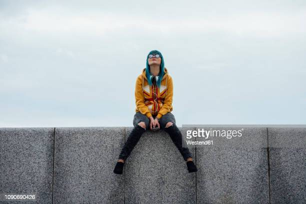 young woman with dyed blue hair sitting on a wall looking up - 個性 ストックフォトと画像