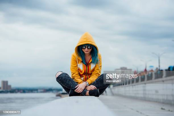 young woman with dyed blue hair sitting on a wall wearing fashionable hooded jacket - yellow coat stock pictures, royalty-free photos & images