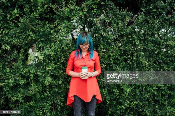 young woman with dyed blue hair standing in front of a hedge with beverage - three quarter length stock pictures, royalty-free photos & images