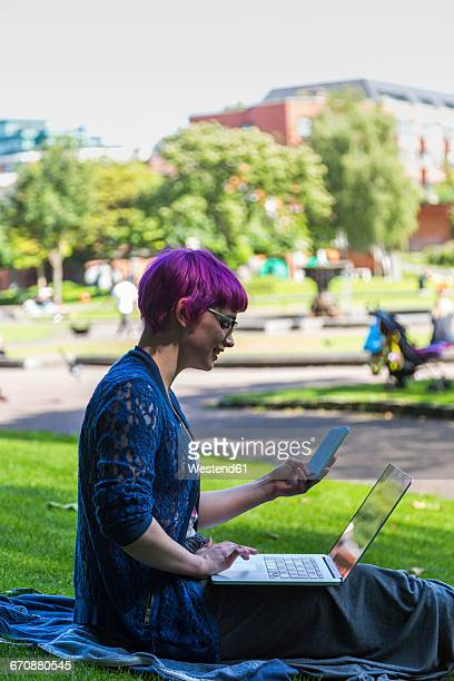Young woman with dyed hair sitting on a meadow using laptop and cell phone