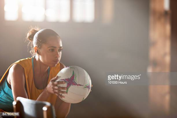 Young woman with earbuds holding netball in gym.