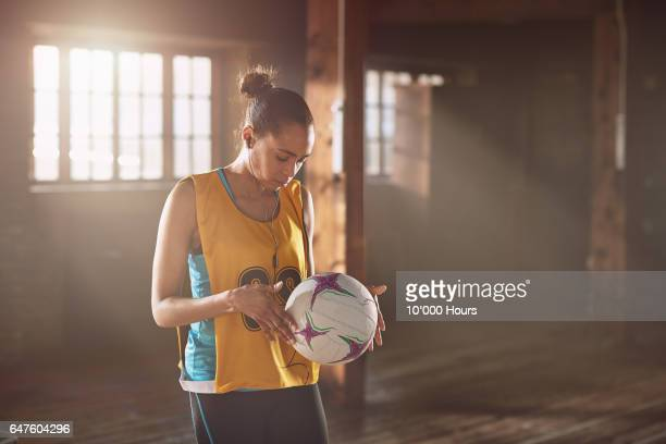 young woman with earbuds holding netball in gym. - girl power provérbio em inglês - fotografias e filmes do acervo