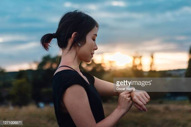 young woman with earphones and smart watch - relaxation exercise stock pictures, royalty-free photos & images