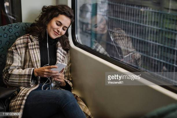young woman with earphones using smartphone on a subway - subway train stock pictures, royalty-free photos & images