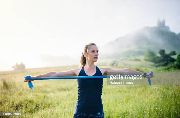 young woman with elastic bands doing exercise outdoors in nature early in the morning. - gummihose stock-fotos und bilder