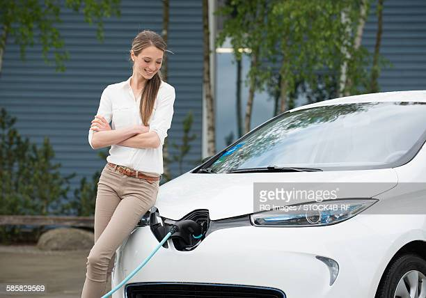 young woman with electric car at ev charging station - elektroauto stock-fotos und bilder