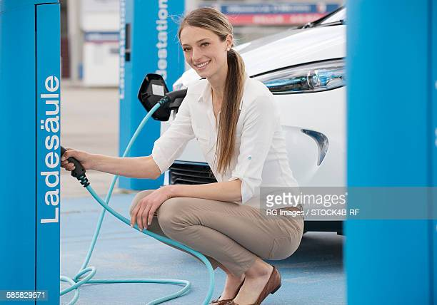 Young woman with electric car at EV charging station