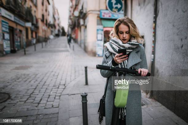 young woman with electric scooter checking her smartphone - electric scooter stock pictures, royalty-free photos & images