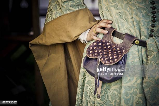 Young woman with embroidered dress and scarsella attached to the belt for storing money or small everyday items 14th century Historical reenactment
