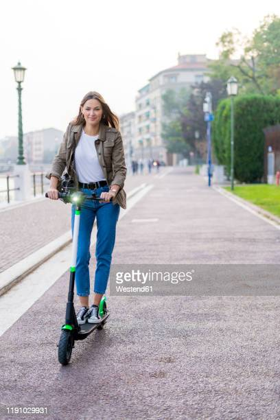 young woman with e-scooter in verona, italy - electric scooter stock pictures, royalty-free photos & images