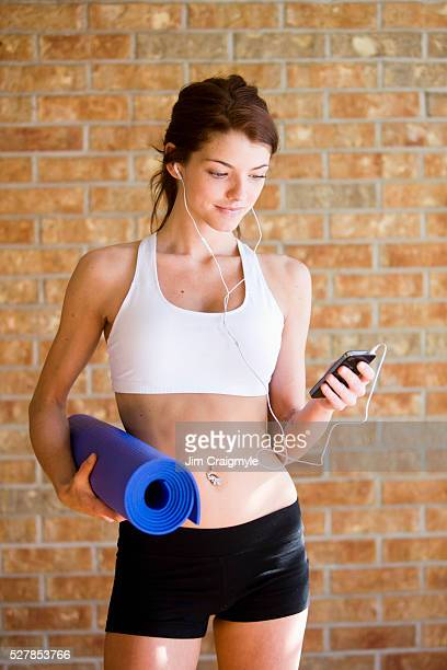 Young woman with exercise mat and mp3 player