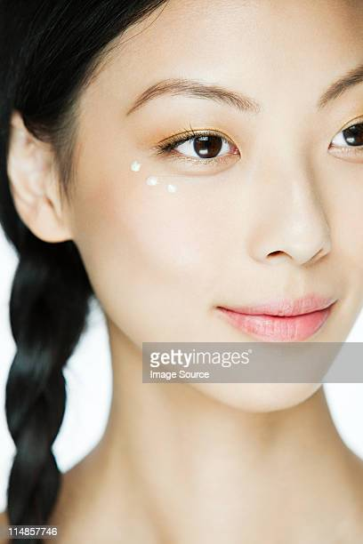 Young woman with eye cream