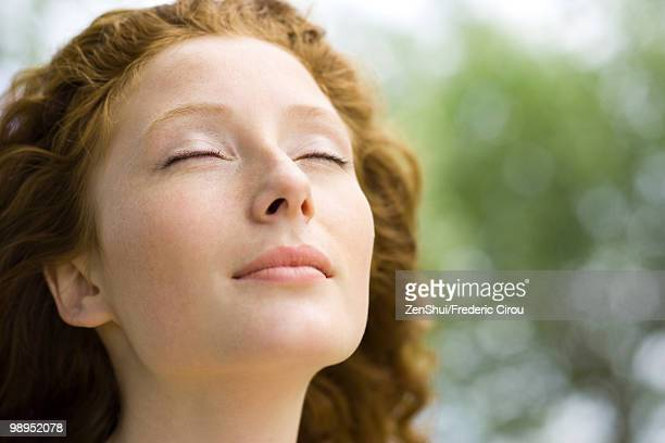 young woman with eyes closed and serene expression on face, portrait - satisfaction fotografías e imágenes de stock