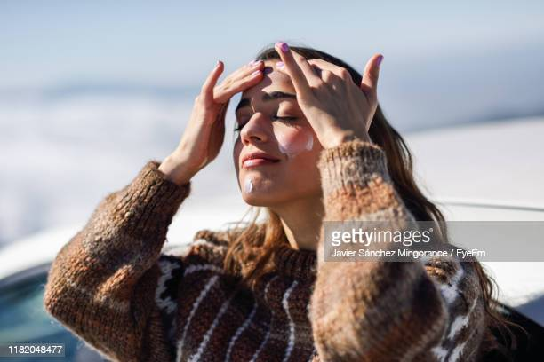 young woman with eyes closed applying moisturizer while standing outdoors during winter - beauty in nature stock-fotos und bilder