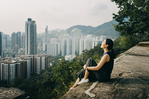Young woman with eyes closed enjoying the tranquility and the spectacular city skyline on the top of mountain - gettyimageskorea
