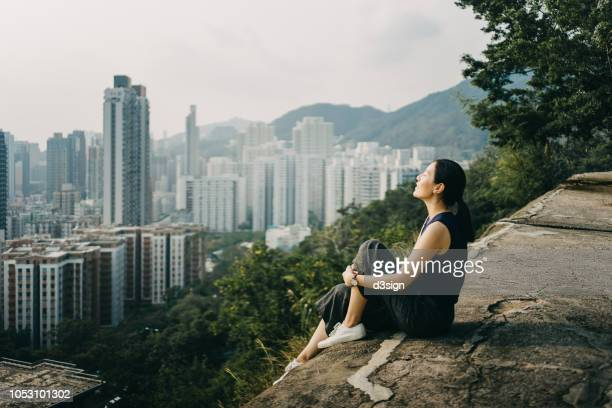young woman with eyes closed enjoying the tranquility and the spectacular city skyline on the top of mountain - prosperity stock pictures, royalty-free photos & images