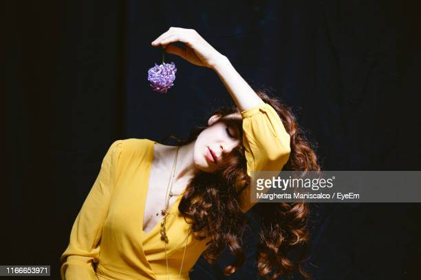 young woman with eyes closed holding flower against black background - glicine foto e immagini stock